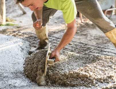 Man leveling wet concrete using a trowel